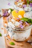 与格兰诺拉麦片,桔子,薄荷和可食的花的酸奶 图库摄影