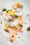 与格兰诺拉麦片,桔子,薄荷和可食的花的酸奶 库存照片