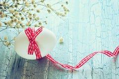 与格子花呢披肩丝带的白色复活节彩蛋 免版税库存图片