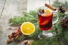 与桂香、桔子和圣诞树的圣诞节热的被仔细考虑的酒在木板 冬天传统饮料 免版税库存照片