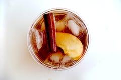 与桂香和苹果切片的刷新的冰茶在塑料杯子 免版税库存图片