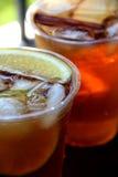 与桂香和苹果切片的刷新的冰茶在塑料杯子 免版税库存照片
