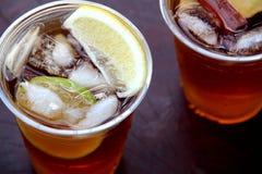 与桂香和苹果切片的刷新的冰茶在塑料杯子 库存照片