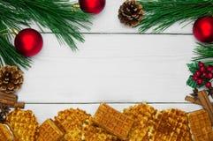 与桂香和茴香和分支圣诞树的奶蛋烘饼和与锥体的红色球在白色木葡萄酒背景 库存图片