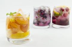 与桃子切片的桃子汁在绿色backgr的一块弯曲的玻璃 库存图片