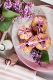 与桃红色丝带、淡紫色花和巧克力牛奶的黄油曲奇饼 免版税库存图片