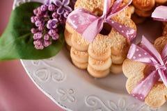 与桃红色丝带和淡紫色花,顶视图的甜曲奇饼 库存照片