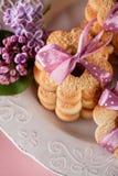 与桃红色丝带和淡紫色花,顶视图的黄油曲奇饼 库存照片