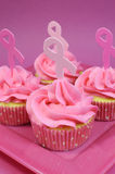与桃红色丝带标志-垂直的桃红色杯形蛋糕 库存图片