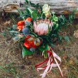 与桃红色丝带的土气婚礼花束在日志附近 附庸风雅 免版税库存照片