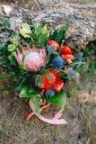 与桃红色丝带的土气婚礼花束在日志附近 附庸风雅 免版税库存图片