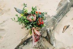 与桃红色丝带的土气婚礼花束在日志,在海滩 特写镜头 艺术品,五谷 免版税库存照片