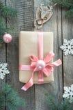 与桃红色丝带的圣诞节礼物和木表面上的灰色毛线衣 圣诞节概念 免版税库存图片
