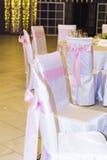 与桃红色丝带的婚礼椅子 库存照片