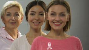 与桃红色丝带的微笑对照相机,乳腺癌控制的另外年龄的妇女 股票视频