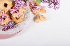 与桃红色丝带的曲奇饼在有淡紫色花的白色板材从 免版税库存照片