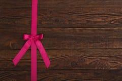 与桃红色丝带的板条木纹理背景 免版税库存照片