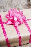与桃红色丝带的礼物在木背景 免版税库存照片