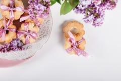 与桃红色丝带的饼干在有淡紫色花的白色板材,上面 库存照片