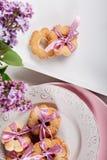 与桃红色丝带的饼干在有淡紫色花的白色板材 图库摄影
