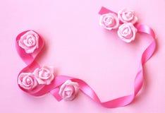 与桃红色丝绸丝带,玫瑰色花的柔和的春天背景 免版税库存照片