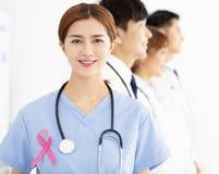与桃红色乳腺癌了悟丝带的医疗队 免版税图库摄影