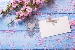 与桃红色佐仓花的在蓝色木头的背景和空标识符 免版税图库摄影