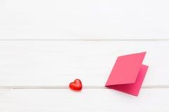 与桃红色卡片的小红色心脏在白色木背景 免版税库存图片