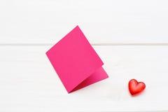与桃红色卡片的小红色心脏在白色木背景 库存图片