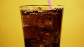 与桃红色吸管的混合的可乐 玻璃有很多焦炭泡沫腾涌的饮料冰块 股票录像