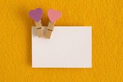 与桃红色和紫色别针的白色板料在黄色背景为情人节 库存图片