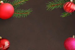 与桃红色和红色波浪愚钝的球的圣诞树分支在黑暗的背景 免版税库存图片