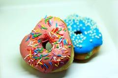 与桃红色和蓝色釉的两个油炸圈饼与小洒 库存图片