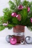 与桃红色和银色中看不中用的物品的圣诞节焦点在棕色花瓶 免版税库存照片