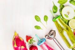 与桃红色和绿色圆滑的人的健康食物在有秸杆和成份的瓶:苹果,石灰,菠菜,草莓,李子, exot 免版税图库摄影