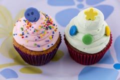 与桃红色和绿色奶油的杯形蛋糕在白色背景 免版税库存图片