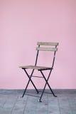 与桃红色墙壁的葡萄酒椅子 库存照片
