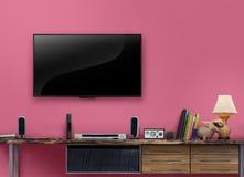 与桃红色墙壁的被带领的电视木桌在客厅 免版税图库摄影