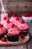 与桃红色奶油、糖心脏和新鲜的莓的巧克力杯形蛋糕为情人节 免版税图库摄影