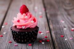 与桃红色奶油、糖心脏和新鲜的莓的巧克力杯形蛋糕为情人节 免版税库存照片