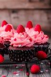 与桃红色奶油、糖心脏和新鲜的莓的巧克力杯形蛋糕为情人节 图库摄影