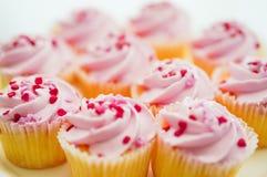 与桃红色奶油和心脏的杯形蛋糕洒 库存照片