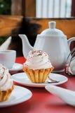 与桃红色奶油和洒的开胃蛋糕在桌上与a 免版税库存照片