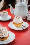 与桃红色奶油和洒的开胃蛋糕在桌上与a 免版税库存图片