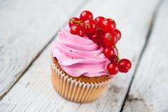 与桃红色奶油和红浆果的杯形蛋糕 免版税图库摄影