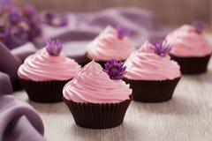 与桃红色奶油和紫罗兰色花的杯形蛋糕传统甜婚礼酥皮点心在葡萄酒背景的行 库存照片