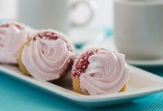 与桃红色奶油的三个蛋糕在一个蓝色背景 库存图片