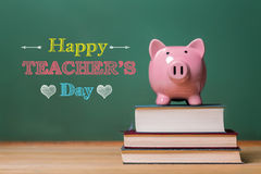与桃红色存钱罐的愉快的老师天消息 免版税库存照片
