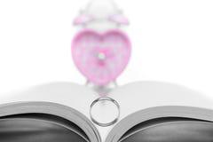 与桃红色心形的时钟的婚戒在白色 免版税库存照片