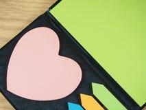 与桃红色心脏形状,在黑笔记本的箭头形状的五颜六色的稠粘的纸 库存图片
